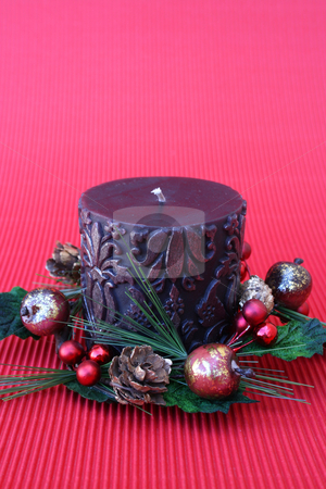 Christmas Wreath stock photo, Dark pattern candle with a wreath on a red background by Vanessa Van Rensburg