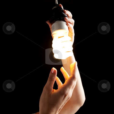 Hand Holding Lightbulb stock photo, A hand holding onto a lightbulb. Square framed shot. by Media Deva