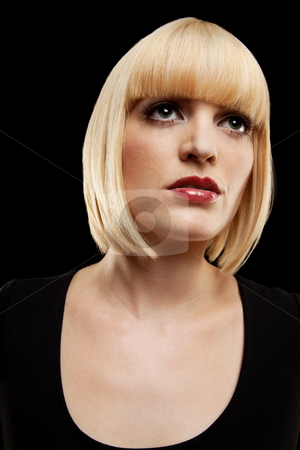 Compelling Blonde Looking Upward stock photo, A compelling blonde woman looking upward.  She is wearing black and has a blank expression on her face. Vertically framed photo. by Media Deva