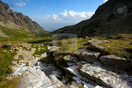Stones in a mountain valley stock photo, Stones in a mountain valley with a lake on horizon by Juraj Kovacik