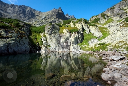 Peak reflecting in a mountain lake stock photo, Stone wall of a peak reflecting in waters of a mountain lake by Juraj Kovacik