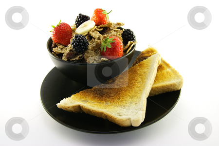 Bran Flakes in a Black Bowl stock photo, Crunchy looking delicious bran flakes and juicy fruit in a black bowl with toast on a white background by Keith Wilson