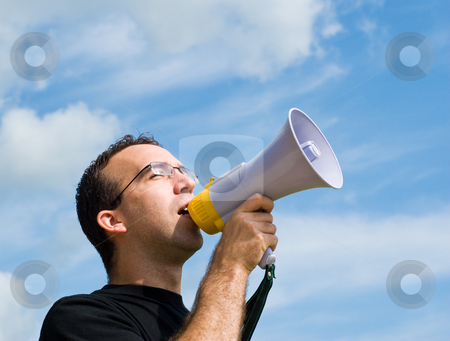 Man Talking Into Megaphone stock photo, A young man wearing glasses is talking into a megaphone outside with blue sky behind him by Richard Nelson