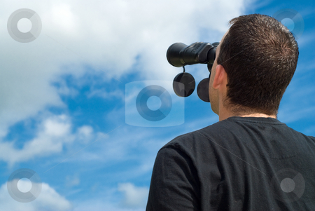 Bird Watcher stock photo, Low angle view of a bird watcher using binoculars with some blue sky and clouds behind him by Richard Nelson