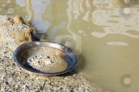 Gold Pan by the River stock photo, A well-used gold pan sits idle on the bank of a river. by Lee Torrens