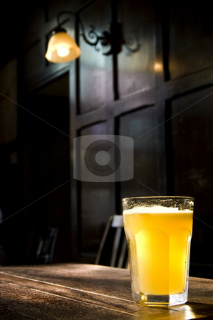 Traditional English Pub stock photo, A lone beer glass in a darkened atmospheric English Pub by Lee Torrens
