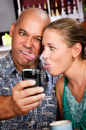 Couple in Coffee House Taking Self-Portrait with Cell Phone stock photo, Attractive couple in a coffee house taking self-portrait with cell phone by Scott Griessel