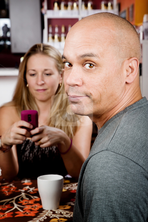Bored man with woman on cell phone stock photo, Bored man with woman on cell phone in coffee house by Scott Griessel