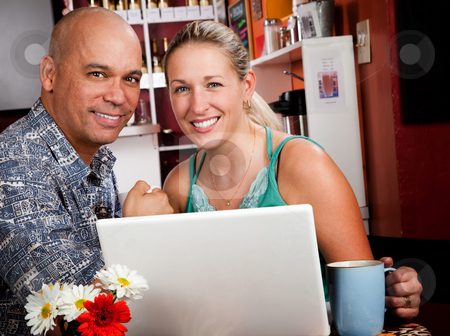 Couple in Coffee House with Laptop Computer stock photo, Attractive couple in a coffee house with laptop computer by Scott Griessel