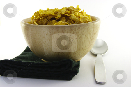 Cornflakes in a Wooden Bowl with Spoon stock photo, Golden crisp cornflakes in a round wooden bowl with a black napkin and a spoon on a white background by Keith Wilson