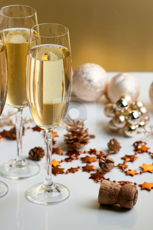 Glasses of champagne stock photo, Three glasses of champagne, christmas balls and ornaments in front of golden background by Alexander Zschach
