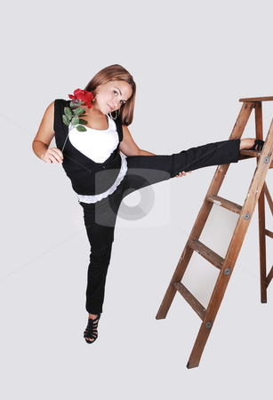 Pretty girl on the stepladder. stock photo, Young, lovely girl in black pants and top, with white shirt holding a red rose in her hand and one leg high on the stepladder, for light gray background. by Horst Petzold