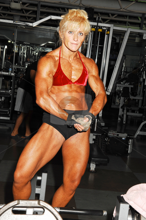 Bodybuilding woman.  stock photo, An very muscular blond bodybuilding woman shoos her muscles on the 