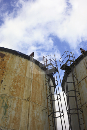 Old storage tanks stock photo, Two old storage tanks under a cloudy sky by Mike Smith