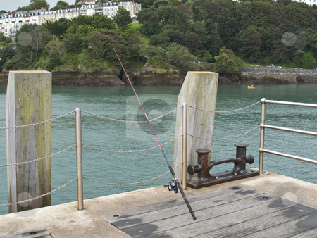 Fishing Rod at end of Pier stock photo, A fishing rod cash out into the harbour at the end of a pier by Stephen Clarke