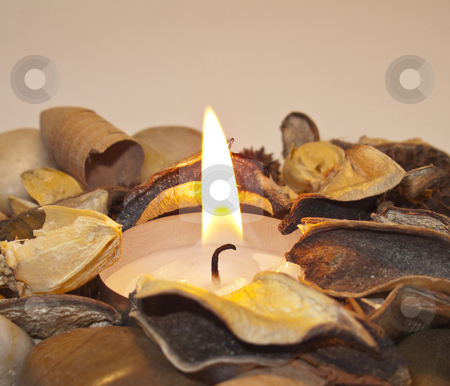 Candle Flame and PoPuri stock photo, A candle flame surrounded by stones and popuri by Stephen Clarke