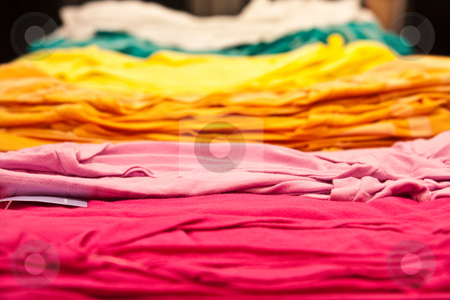 So Many T-Shirts stock photo, A stack of colorful t-shirts on a table. by Tyson Koska