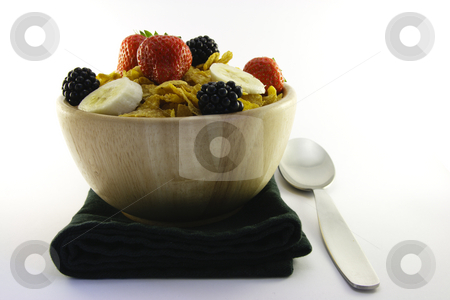 Cornflakes and Fruit with Napkin and Spoon stock photo, Cornflakes with strawberries, blackberries and banana in a round wooden bowl with a black napkin and spoon on a white background by Keith Wilson