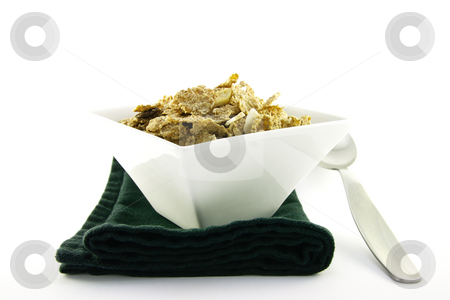 Bran Flakes in a White Bowl stock photo, Crunchy delicious looking bran flakes in a white bowl with a spoon and a black napkin on a white background by Keith Wilson