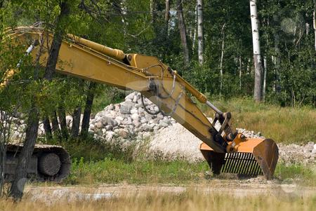 Excavator Shovel stock photo, An excavator shovel with a pile of stones behind by Richard Nelson
