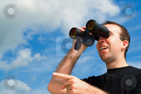 Bird Watching stock photo, A man bird watching with a set of binoculars and is pointing with his finger by Richard Nelson