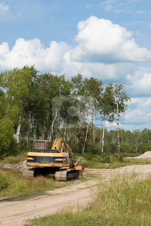 Excavator stock photo, An excavator parked on the side of a gravel road near a job site by Richard Nelson