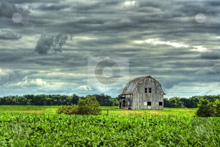 Barn in Scenic Rural Landscape in HDR stock photo, Old rustic barn next to field done in hdr by Dennis Crumrin