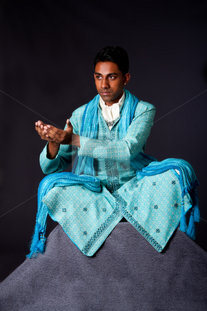 Hindu man sitting in lotus position stock photo, Beautiful authentic Indian hindu man in typical ethnic groom attire sitting in lotus position with legs crossed on top of rock and sticking hands out to receive a gift. Bangali male wearing a light blue agua decorated Dhoti with shawl. by Paul Hakimata