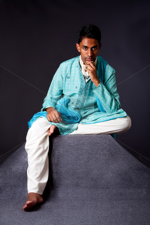 Hindu man sitting and thinking stock photo, Beautiful authentic Indian hindu man in typical ethnic groom attire sitting and thinking on top of pyramid rock. Bangali male wearing a light blue agua decorated Dhoti with shawl. by Paul Hakimata
