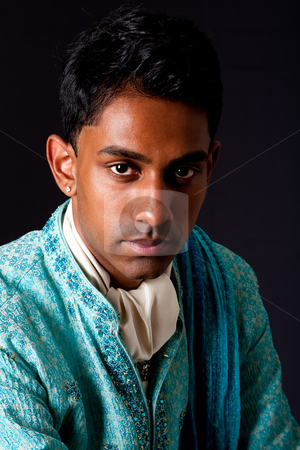 Handsome Hindu man stock photo, Beautiful face of an Indian Hindu young man with earring wearing blue Dhoti. Portrait of handsome Desi male, isolated. by Paul Hakimata