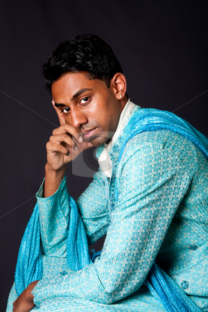 Hindu man sitting and thinking stock photo, Beautiful face of an Indian Hindu young man with earring wearing blue Dhoti. Portrait of handsome Desi male sitting and thinking, isolated. by Paul Hakimata