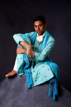 Hindu man sitting on rock stock photo, Beautiful authentic Indian hindu man in typical ethnic groom attire sitting relaxed on top of rock leaning on knee. Bangali male wearing a light blue agua decorated Dhoti with shawl. by Paul Hakimata