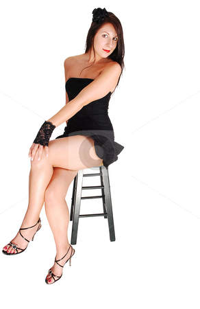 Pretty girl in black dress. stock photo, Young lovely girl in a short black dress with red lips and high heels sitting in the studio for white background. by Horst Petzold