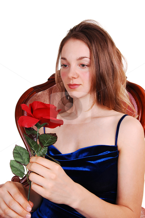 Beautiful woman with red rose. stock photo, A very pretty young girl in an royal blue dress and gorgeous long red hair sitting in a pink armchair, holding a red rose to her face, on white background. by Horst Petzold