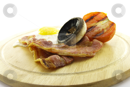 Breakfast on a Wooden Plate stock photo, Slices of crispy pork bacon with half a grilled tomato a fried egg and a mushroom on a wooden round plate with a white background by Keith Wilson