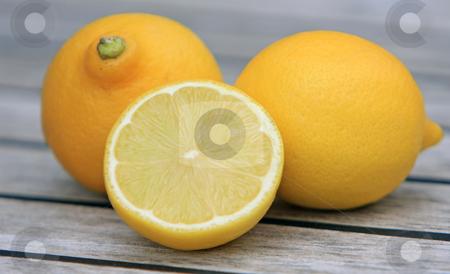 Lemons stock photo, Three lemons on wooden table by Karen Arnold