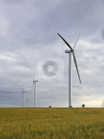 Wind turbines stock photo, A row of wind turbines under a cloudy sky by Mike Smith