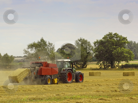 Bailing straw stock photo, A tractor baling straw in summer by Mike Smith