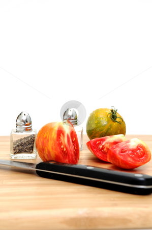 Sliced Heirloom Tomato stock photo, Heirloom tomatoes cut into wedges on a wooden cutting board with paring knife and salt and perrper shakers by Lynn Bendickson