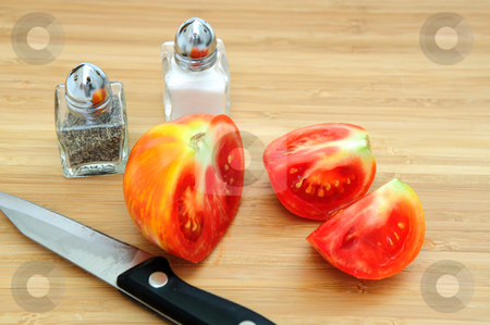Red And Yellow Heirloom Tomato stock photo, Heirloom tomatoes cut into wedges on a wooden cutting board with paring knife and salt and perrper shakers by Lynn Bendickson
