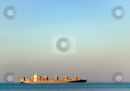 Container transportation stock photo, Loaded ship transporting containers on blue water by Wino Evertz