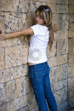 Beautiful young woman posing on wall stock photo, Beautiful young model posing on wall by Desislava Dimitrova