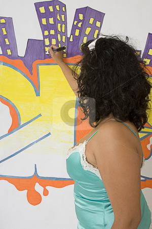 Women writting on wall stock photo, Twenty something latino women drawing on a graffitied wall by Yann Poirier