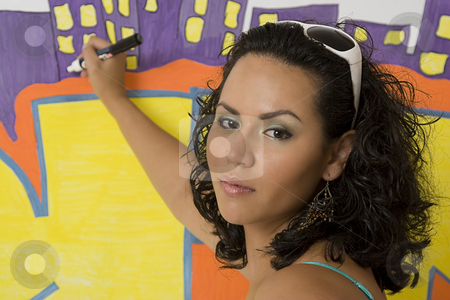 Women writting on wall stock photo, Twenty something latino women sitting in front of a graffiti by Yann Poirier