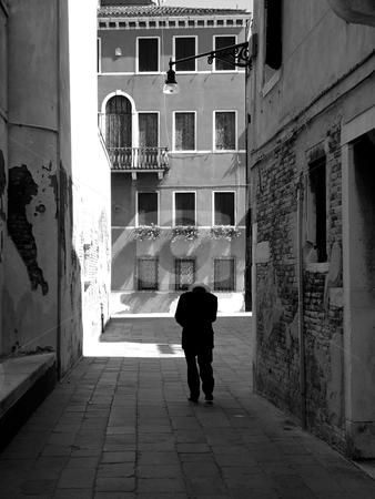 Lonely old man in Italy stock photo, Classical Italy photo in black and white. Old man walking in a dark alley on a sunday morning. by Peter Van veldhoven