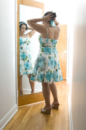 Adjusting hair stock photo, Latino women looking at a reflection in a mirror and adjusting her hair by Yann Poirier