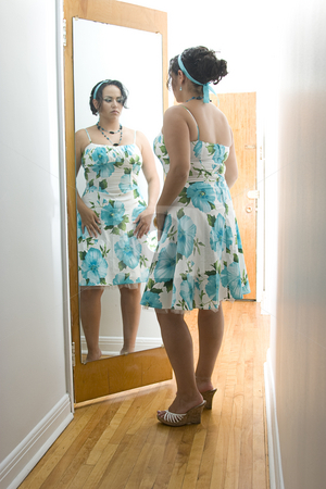 Adjusting dress stock photo, Latino women adjusting her dress in the reflection of a mirror by Yann Poirier