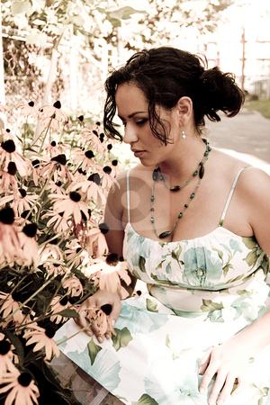 Smelling daisies stock photo, Twenty something columbian women smelling daisies in a garden by Yann Poirier