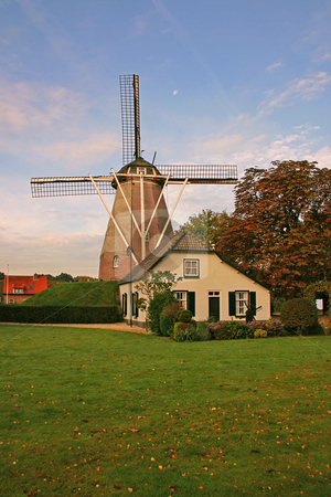 House and windmill in the Netherlands vertical stock photo, House and windmill in the Netherlands with green grass and blue sky vertical by Stephen Goodwin
