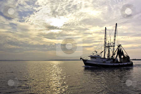 Fishing trawler on the water at sunrise stock photo, Fishing trawler on the water and dramatic clouds at sunrise by Stephen Goodwin